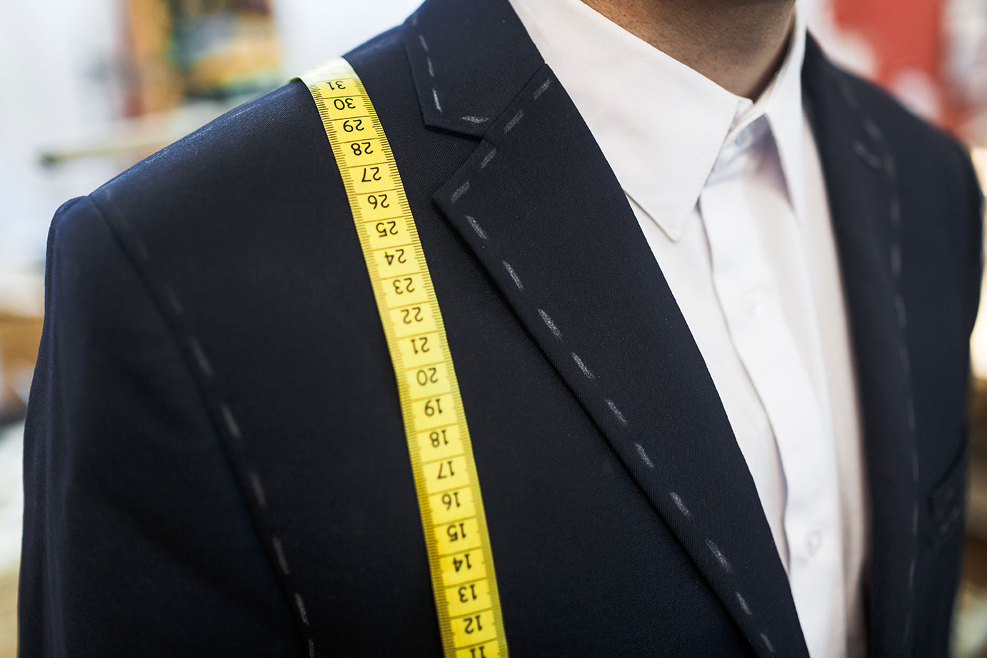 new-jacket-and-measuring-tape-on-businessman_rLWlNuBDRW